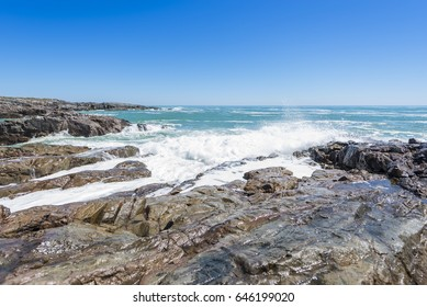 White ocean waves crashing over coastal sea rocks in summer