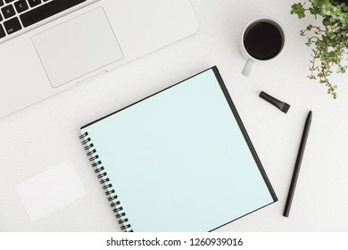 White office desk with blank notebook, pen, laptop, plan and coffee cup. Flat lay