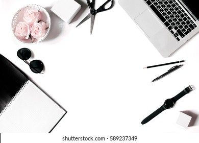 White office desk frame with laptop keyboard and supplies. Laptop, notebook, pen, roses, sunglasses, pencil, scissors, watch and office supplies on white background. Flat lay, top view, mockup