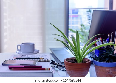 White office desk with laptop, green flower, smartphone, cup of coffee at modern workplace / Business background concept