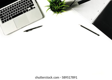 White office desk with laptop keyboard and supplies. Laptop, notebook, pen, clips, pencil, plant and office supplies on white background. Flat lay, top view, mockup