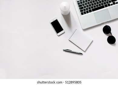 White office desk with laptop, smartphone, sunglasses and notebook . Top view with copy space, flat lay.