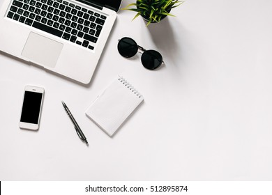 White office desk with laptop, smartphone, office plant and notebook . Top view with copy space, flat lay.