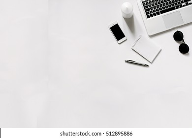 White office desk with laptop, smartphone and notebook . Top view with copy space, flat lay.