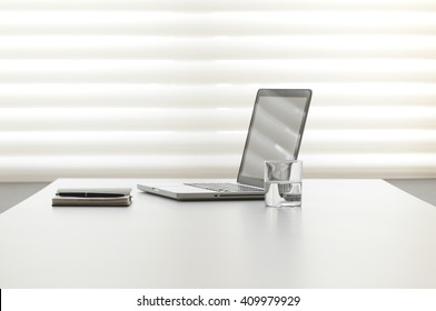 white office desk with note pad and laptop