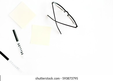 White office desk with paper blank and glasses on white background. Flat lay, top view, mockup