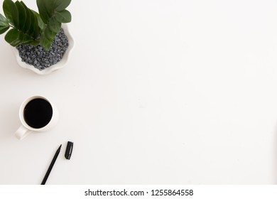White office desk with office plant, coffee and pen. Top view with copy space, flat lay