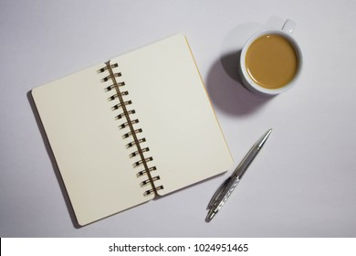 White office desk with spiral notebook, silver pen and a cup of coffee, flat lay