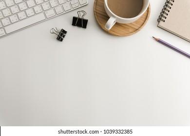 Weißer Schreibtisch mit leerem Notebook, Computer, Zubehör und Kaffeetasse. Draufsicht mit Kopienraum. Flat lay.