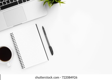White office desk table with blank notebook, pen and cup of coffee. Top view with copy space, flay lay.