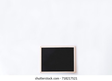 White office desk table with chalkboard. Top view with copy space, flat lay.