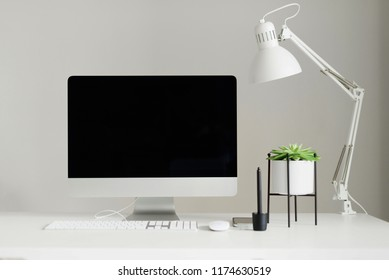 White office desk table with computer keyboard, mouse, monitor, graphic tablet, smartphone, succulent plant and other office supplies. Top view, copy space, flat lay