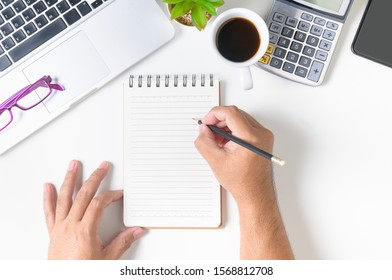White office desk table with hand man writing something on blank notebook page. Top view, flat lay.
