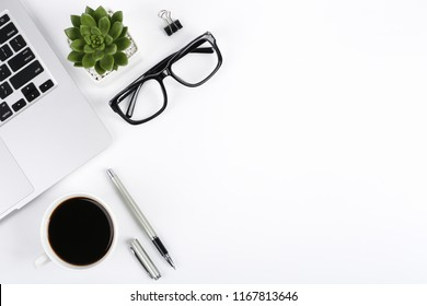 White office desk table with laptop computer, green plant, glasses and a cup of coffee. Top view with copy space, flat lay.