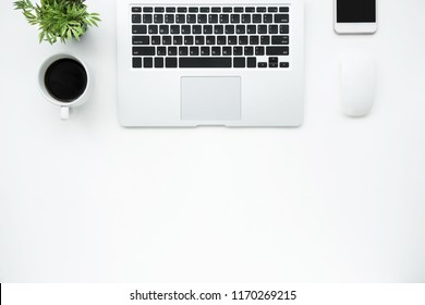 White office desk table with laptop computer, coffee cup and sup