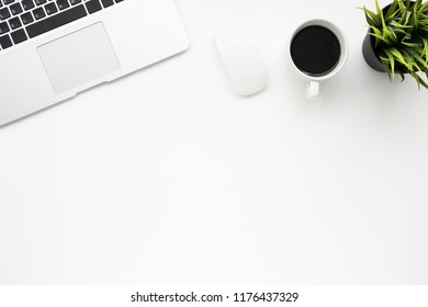 White office desk table with laptop, cup of coffee and supplies. Top view with copy space, flat lay.