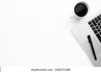 White office desk table with laptop computer, cup of coffee and pen. Top view with copy space, flat lay.