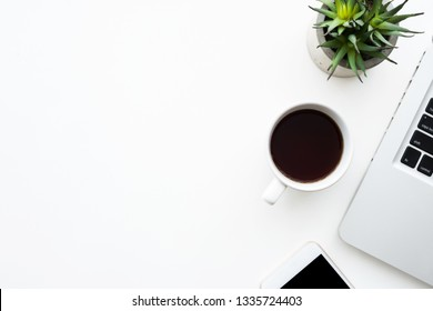 White office desk table with laptop computer, cup of coffee and smartphone. Top view with copy space, flat lay.