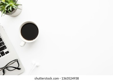 White office desk table with laptop computer, cup of coffee, eye glasses and supplies. Top view with copy space, flat lay.