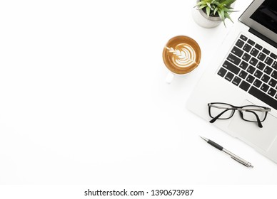 White office desk table with laptop computer, cup of coffee, pen and eye glasses. Top view with copy space, flat lay.