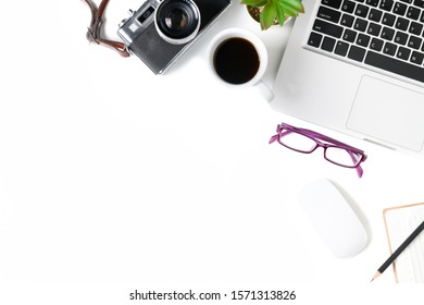 White office desk table with laptop computer and vintage camera, cup of coffee and glasses. Top view with copy space, flat lay.