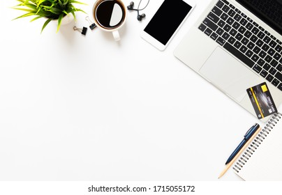 White office desk table with laptop, and smartphone with equipment other office supplies, credit card shopping online concept with copy space, top view