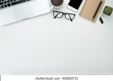 White office desk table with laptop, cup of coffee and supplies. Top view with copy space.