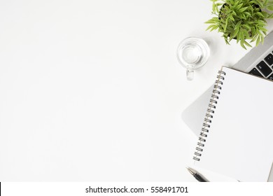 White office desk table with laptop, notebook and supplies. Top view with copy space, flat lay.