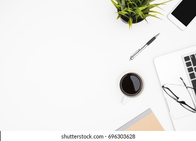 White office desk table with laptop, cup of coffee and supplies. Top view with copy space, flay lay.