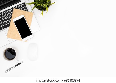 White office desk table with laptop, smartphone, cup of coffee and supplies. Top view with copy space, flat lay.