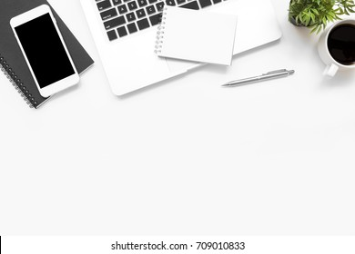 White office desk table with laptop computer, smartphone with blank screen, notebook and supplies. Top view with copy space, flat lay.