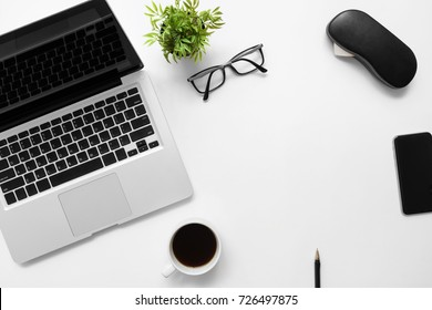 White office desk table with laptop computer, cup of coffee and office supplies. Top view with copy space, flat lay.