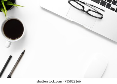 White office desk table with laptop, cup of coffee and office supplies. Top view with copy space, flay lay.