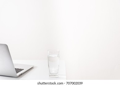 White office desk table with notebook, glass of water, laptop with right side free space on white background.