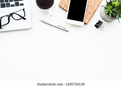 White office desk table with smartphone, laptop computer, cup of coffee and supplies. Top view with copy space, flat lay.