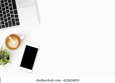 White office desk table with smartphone, laptop computer and cup of coffee. Top view with copy space, flat lay.