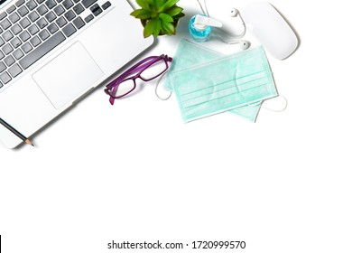 White office desk table with surgical face mask and sanitizer bottle or alcohol gel with laptop isolated on white background, work from home and covid-19 concept and new normal