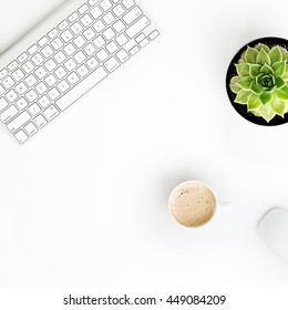 White office desk table with wireless aluminum keyboard, mouse, cup of coffee and succulent flower in pot. Top view with copy space. Flat lay.