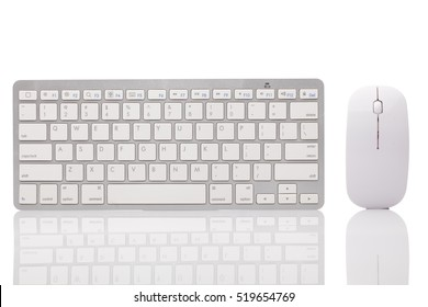 White office desk table with wireless aluminum keyboard, mouse