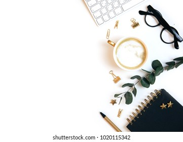 White office desk workspace with coffee, paper blank, green leaves and office supplies. Flat lay, top view, mockup.