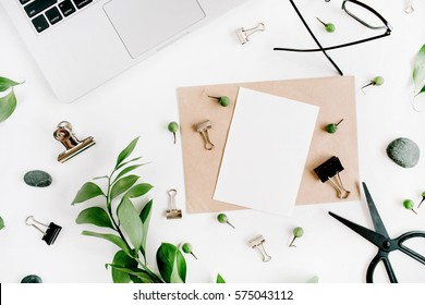 White office desk workspace with paper blank, green leaves and office supplies. Laptop, scissors, glasses on white background. Flat lay, top view, mockup.