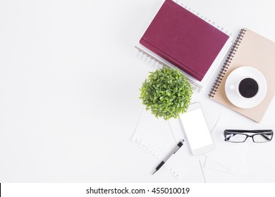 White office desktop with blank smartphone, glasses, coffee cup, spiral notepads, book, decorative plant and other items. Top view, Closeup, Mock up