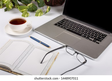 White office desktop with opened notebook, laptop cpmputer and accessories