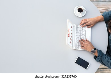 White Office Round Table and Man Working on Computer Top View Casual Clothing Typing on Keyboard with Marketing Chart on Screen Smart Phone and Cup of Coffee aside
