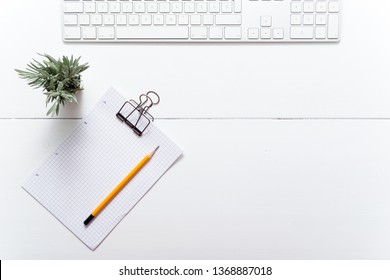 white office table, computer keyboard and little lavender plant, note papers, pencil