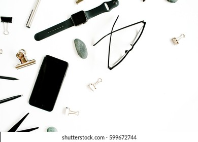 White office table desk with supplies. mobile phone, glasses, scissors and office supplies on white background. Flat lay, top view office table desk.
