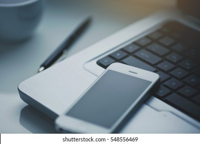 White office table with laptop, coffee, smartphone and pen.