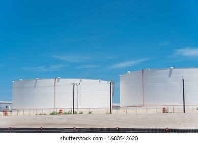 White oil storage tank with stairs under cloud blue sky in Corpus Christi, Texas, America. Large industrial container for petrol, oil, natural gas. Tank farm at petrochemical, oil refinery plant
