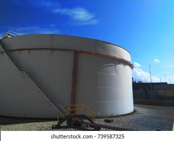 White Oil tanking within tank farm and blue sky. large tanks for petrol and oil. large white tanks for petrol and oil