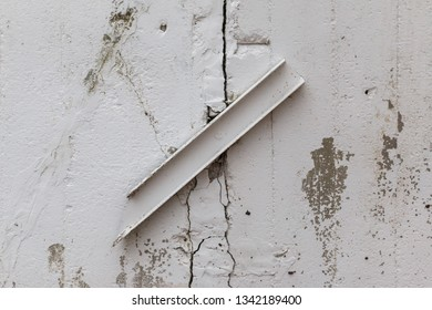 white old cracked wall joined by a metal strip. crack fighting concept. problem of destruction of buildings